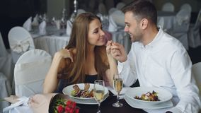 Happy loving couple is holding hands, talking and kissing during romantic dinner in restaurant. Affectionate