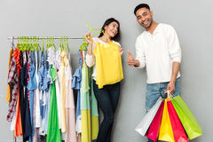 Happy loving couple holding shopping bags and showing thumbs up. Royalty Free Stock Images