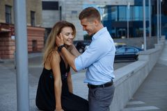 Happy loving couple hugging, date in the city. black dress, blue shirt and gray pants.attraction.the man picked up the woman`s. Attraction.happy loving couple royalty free stock image
