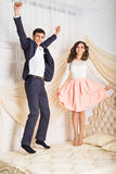 Happy loving couple jumping and having fun in bed Royalty Free Stock Images
