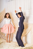 Happy loving couple jumping and having fun in bed stock images
