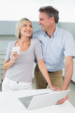 Happy loving couple with laptop in kitchen Royalty Free Stock Photo