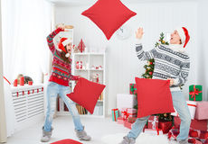 Happy loving couple laughing and fighting on pillows on Christma Royalty Free Stock Image