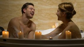 Happy loving couple laughing and having fun in bath, romantic evening, spa. Stock footage stock footage