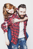 Happy loving couple. Life style, happiness and people concept: Happy loving couple. Young men piggybacking his girlfriend. Studio shot over white background Royalty Free Stock Image