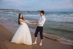 Happy loving couple newlyweds hold each others hands on ocean beach. Beautiful bride and groom at wedding day outdoors royalty free stock photo