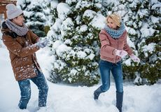 Carefree young guy and guying enjoying winter snow. Happy loving couple playing snowballs in park. Man is throwing snowball on running women and smiling Stock Images