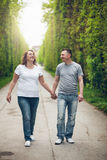 Happy loving couple on a romantic walk outdoors in park Royalty Free Stock Images