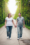 Happy loving couple on a romantic walk outdoors in park Royalty Free Stock Image