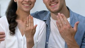 Happy loving couple showing engagement rings on fingers, future family, joy. Stock footage stock footage
