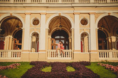 Happy loving couple sitting outside at balcony of Odessa Opera House. Man is pointing with his finger at something. Interesting which is far away Royalty Free Stock Images