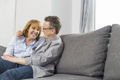 Happy loving couple sitting on sofa at home Stock Photography
