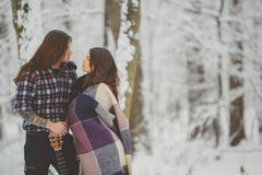 Happy loving couple in snowy winter forest Stock Photos