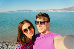Happy loving couple taking self-portrait on beach Stock Photo