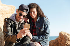 Happy loving couple walking outdoors at beach chatting by phone. Stock Images