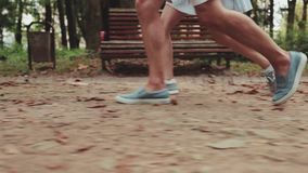 Close up legs of people fleeing the park. Happy Loving Couple Walking A Park. Legs are coming stock video