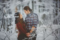 Loving couple walking in snowy winter forest Royalty Free Stock Photo