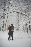 Happy loving couple walking in snowy winter forest Royalty Free Stock Photography