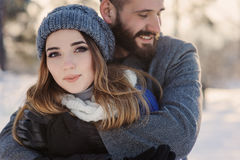 Happy loving couple walking in snowy winter forest, spending christmas vacation together. Outdoor seasonal activities. Stock Photos