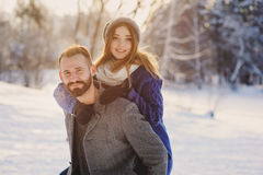 Happy loving couple walking in snowy winter forest, spending christmas vacation together. Outdoor seasonal activities. Lifestyle capture Royalty Free Stock Image