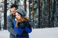 Happy loving couple walking in snowy winter forest, spending christmas vacation together. Outdoor seasonal activities Stock Photo