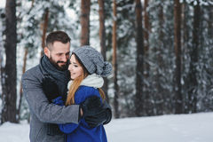 Happy loving couple walking in snowy winter forest, spending christmas vacation together. Outdoor seasonal activities Royalty Free Stock Photo