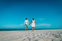 Happy loving couple walking on tropical beach. Vacation royalty free stock images