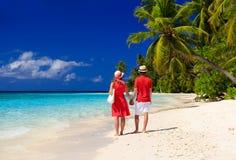 Happy loving couple walking on tropical beach Stock Photos