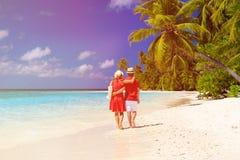 Happy loving couple walking on tropical beach Stock Image