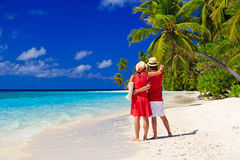 Happy loving couple walking on tropical beach Stock Image