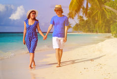 Happy loving couple walking on tropical beach Stock Photos