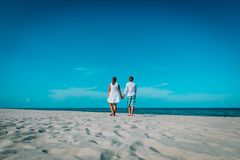 Happy loving couple walking on tropical beach. Vacation stock photography