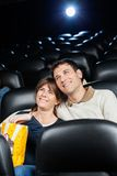 Happy Loving Couple Watching Film In Theater Royalty Free Stock Images