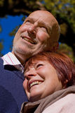 Happy loving elderly couple. Wife nestling to her husband Stock Photo