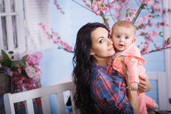 Happy loving family. Cute little girl is combing her mother`s hair stock image