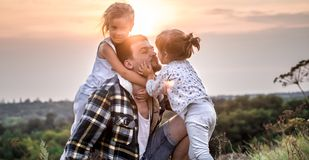 Dad playing with two little cute daughters stock photography