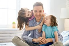 Happy father`s day. Happy loving family. Daddy and his daughters children girls playing together. Father`s day concept stock photo