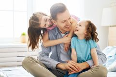 Happy father`s day. Happy loving family. Daddy and his daughters children girls playing together. Father`s day concept royalty free stock images