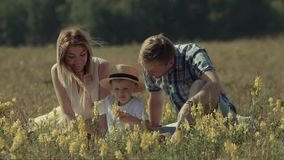 Happy loving family enjoying their time in nature. Parents bend to kiss their adorable child stock video footage