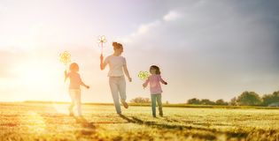Mother and two daughters are playing on meadow Stock Images