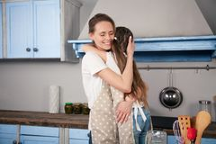 Happy loving family in the kitchen are hugging while preparing bakery together. Mother and child daughter girl are stock photography