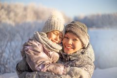 Mother and child girl having fun, playing and laughing on snowy winter. stock photos