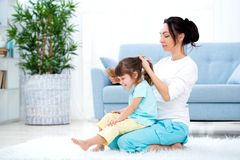 Happy loving family. Mother is combing her daughter`s hair sitting on the carpet on the floor in the room.  royalty free stock photos