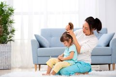 Happy loving family. Mother is combing her daughter`s hair sitting on the carpet on the floor in the room.  royalty free stock photo