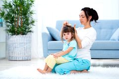 Happy loving family. Mother is combing her daughter`s hair sitting on the carpet on the floor in the room stock image