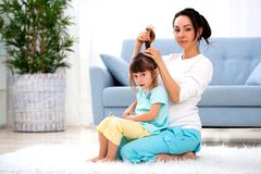 Happy loving family. Mother is combing her daughter`s hair sitting on the carpet on the floor in the room.  royalty free stock photography
