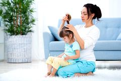 Happy loving family. Mother is combing her daughter`s hair sitting on the carpet on the floor in the room.  royalty free stock image