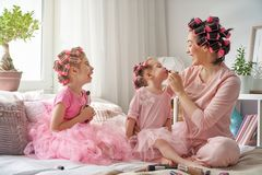 Mom and children doing makeup. Happy loving family. Mother and daughters are doing hair and having fun. Mom and children doing makeup sitting on the bed in the Royalty Free Stock Image