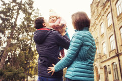 Happy loving family(mother, father and little daughter kid) outdoors walking having fun on a park in autumn season. Fallen yellow royalty free stock images
