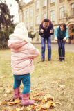 Happy loving family(mother, father and little daughter kid) outdoors walking having fun on a park in autumn season. Fallen yellow royalty free stock photo